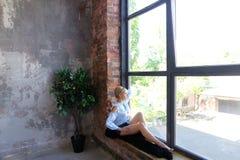 Привлекательная молодая женщина представляет с улыбкой и сидит на силле окна Стоковое Изображение RF