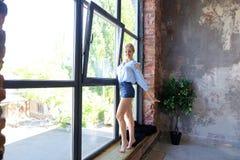 Привлекательная молодая женщина представляет с улыбкой и стоит на sil окна Стоковое Изображение RF