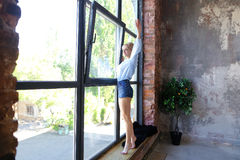 Привлекательная молодая женщина представляет с улыбкой и стоит на sil окна Стоковые Фотографии RF