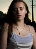 Привлекательная молодая женщина представляя на улице с тенью на ее f Стоковые Изображения RF