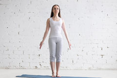 Привлекательная молодая женщина пригонки делая представление горы в белую просторную квартиру стоковое фото