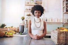 Привлекательная молодая женщина работая на баре сока Стоковые Изображения RF