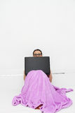Привлекательная молодая женщина работая на ее компьтер-книжке дома Стоковая Фотография
