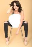 Привлекательная молодая женщина сидя на стуле в ботинках высокой пятки и Стоковое Изображение