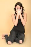 Привлекательная молодая женщина смотря прищурясь через пальцы Стоковое Фото
