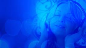 Привлекательная молодая женщина с предпосылкой наушников голубой абстрактной Стоковые Изображения RF