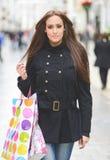 Привлекательная молодая женщина с хозяйственными сумками в коммерчески улице Стоковое фото RF