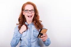 Привлекательная молодая женщина любит чего она видит на smartphone Стоковое Изображение