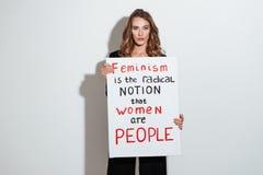 Привлекательная молодая кавказская дама держа пустой с текстом о феминизме Стоковое Изображение RF