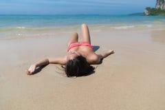 Привлекательная молодая кавказская женщина в купальнике лежа на пляже, празднике океана моря песка девушки влажном Стоковое Фото