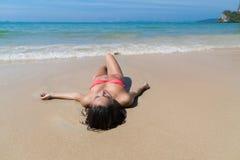 Привлекательная молодая кавказская женщина в купальнике лежа на пляже, празднике океана моря песка девушки влажном Стоковые Фотографии RF