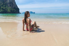 Привлекательная молодая кавказская женщина в купальнике сидя на вид сзади задней части пляжа, празднике морской воды девушки голу Стоковое фото RF