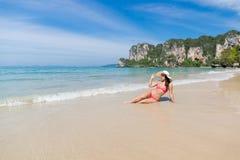 Привлекательная молодая кавказская женщина в купальнике сидя на пляже, празднике морской воды шляпы носки девушки голубом Стоковое Изображение RF