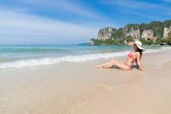 Привлекательная молодая кавказская женщина в купальнике сидя на пляже, празднике морской воды шляпы носки девушки голубом Стоковые Фотографии RF