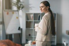 Привлекательная молодая коммерсантка держа чашку и смотря прочь в офисе Стоковая Фотография