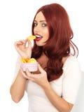 Привлекательная молодая красная с волосами женщина есть хрустящие корочки картошки Стоковые Изображения
