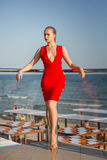 Привлекательная молодая модель в ярком красном платье представляет на голубой предпосылке моря Очаровательная девушка с совершенн Стоковая Фотография RF