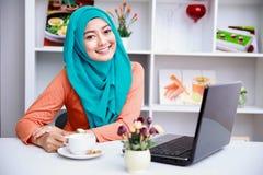 Привлекательная молодая мусульманская женщина наслаждаясь чашкой чаю пока использующ Стоковая Фотография RF