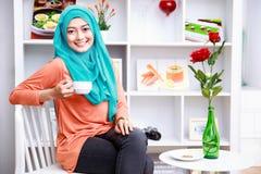 Привлекательная мусульманская женщина наслаждаясь чашкой чаю на украшенном livin Стоковое фото RF