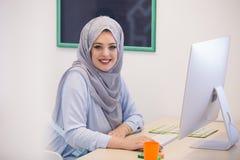 Привлекательная мусульманская молодая женщина работая в офисе на компьютере стоковое фото