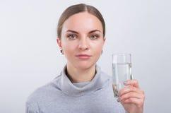 Привлекательная питьевая вода девушки на светлой предпосылке Стоковые Фотографии RF