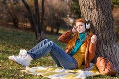 Привлекательная расслабленная дама слушая к музыке сидя под деревом Стоковые Изображения
