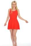 Привлекательная сексуальная шаловливая молодая белокурая женщина нося короткое красное мини платье Стоковые Фото