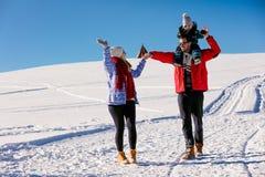 Привлекательная семья имея потеху в парке зимы на горе Стоковая Фотография