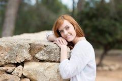 Привлекательная склонность женщины против каменной стены Стоковые Фотографии RF