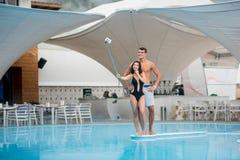 Привлекательная счастливая женщина представляя около бассейна делая фото selfie с monopod и человека стоя за ей на курорте Стоковая Фотография RF