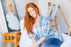 Привлекательная счастливая женщина сидя на белой погремушке в художественной мастерской стоковая фотография