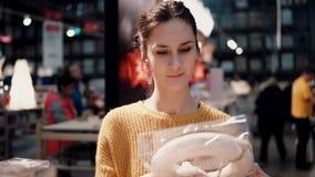 Привлекательная счастливая молодая женщина выбирает на венке рождества магазина оформление для домашнего интерьера Стоковые Изображения