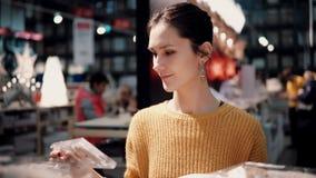 Привлекательная счастливая молодая женщина выбирает на венке рождества магазина оформление для домашнего интерьера Стоковая Фотография