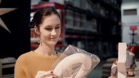 Привлекательная счастливая молодая женщина выбирает на венке рождества магазина оформление для домашнего интерьера Стоковые Фотографии RF