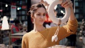 Привлекательная счастливая молодая женщина выбирает на венке рождества магазина оформление для домашнего интерьера Стоковое Изображение RF