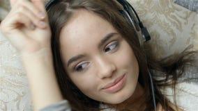 Привлекательная Темн-с волосами женщина слушая к музыке видеоматериал