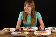 Привлекательная усмехаясь женщина сидя на таблице с кренами Стоковое Изображение RF