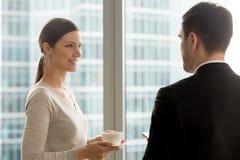 Привлекательная усмехаясь коммерсантка слушая к talkin бизнесмена Стоковая Фотография RF