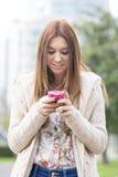 Привлекательная усмехаясь маленькая девочка используя телефон в улице. стоковая фотография