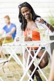 Привлекательная чернокожая женщина сидя на таблице кафа outdoors и drin Стоковое Фото