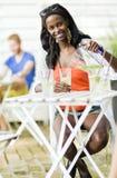 Привлекательная чернокожая женщина сидя на таблице кафа outdoors и drin Стоковые Изображения