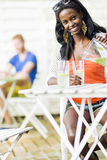 Привлекательная чернокожая женщина сидя на таблице кафа outdoors и drin Стоковое Изображение