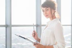 Привлекательная честолюбивая коммерсантка стоя в современном офисе, держащ бумажную папку, смотрящ камеру, усмехаясь Стоковое Фото