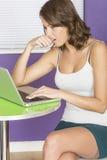 Привлекательная Concerned confused потревоженная сдерживая молодая женщина ногтя используя портативный компьютер Стоковое Изображение RF