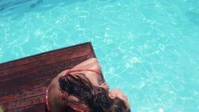 Привлекательное брюнет сидя бассейном и тряся голову видеоматериал