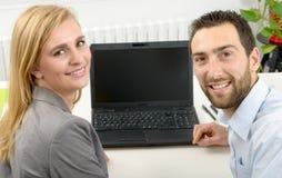 Привлекательное дело человека и женщины используя портативный компьютер Стоковые Фотографии RF