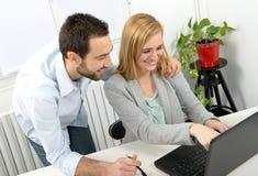 Привлекательное дело человека и женщины используя портативный компьютер Стоковое Изображение RF