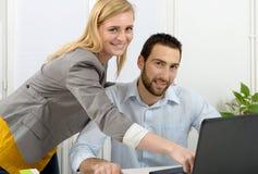 Привлекательное дело человека и женщины используя портативный компьютер Стоковая Фотография RF