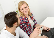 Привлекательное дело человека и женщины используя портативный компьютер Стоковая Фотография