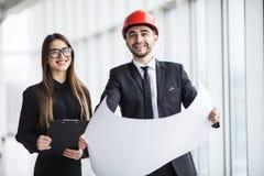 Привлекательное дело человека и женщины объединяется в команду работая конструкция на строительной площадке около панорамных окон Стоковое Фото